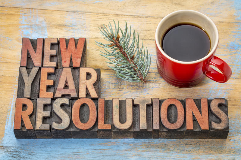 New Year resolutions. Word abstract in vintage letterpress wood type with a cup of coffee and a twig of silver spruce stock photography