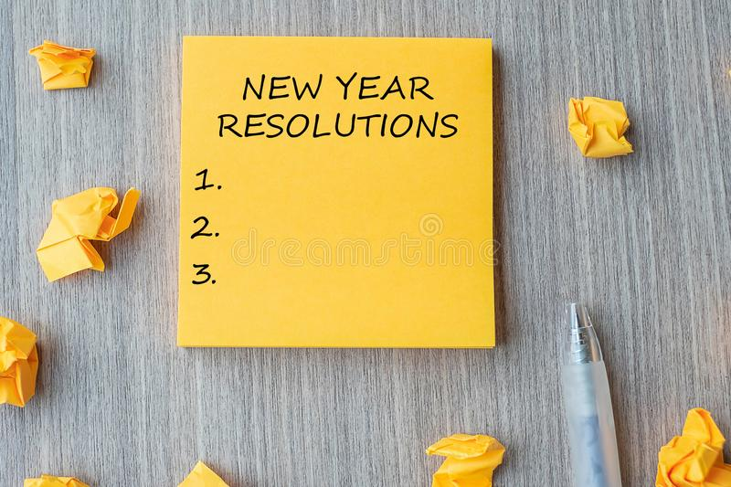 NEW YEAR RESOLUTIONS word on yellow note with  pen and crumbled paper on wooden table background. New start, Strategy and Goal stock photos