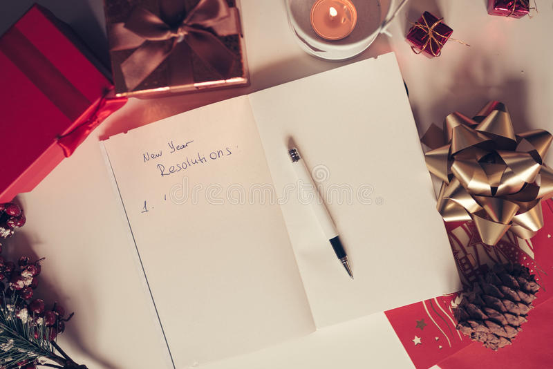 New year resolutions written on notebook with new years decorations stock image