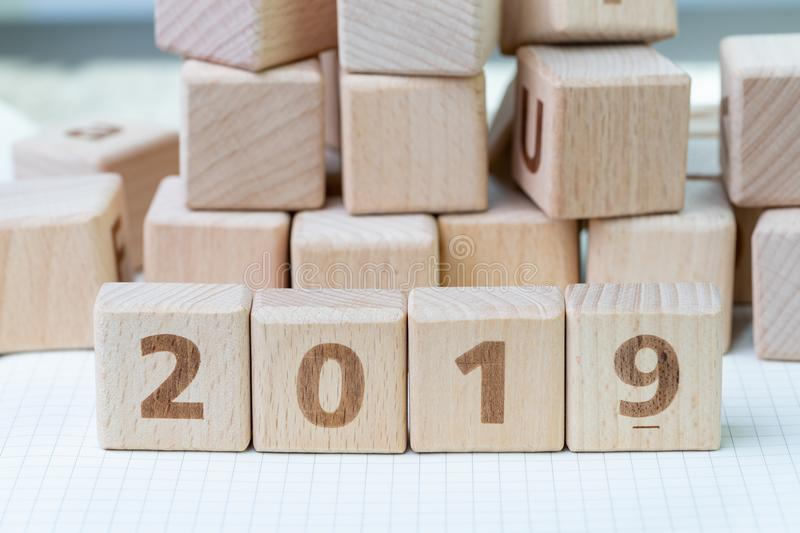 New year 2019, review or resolution concept, cube wooden block w. Ith alphabet building the numbers 2019 on grid line notebooks with other random block in the stock photos