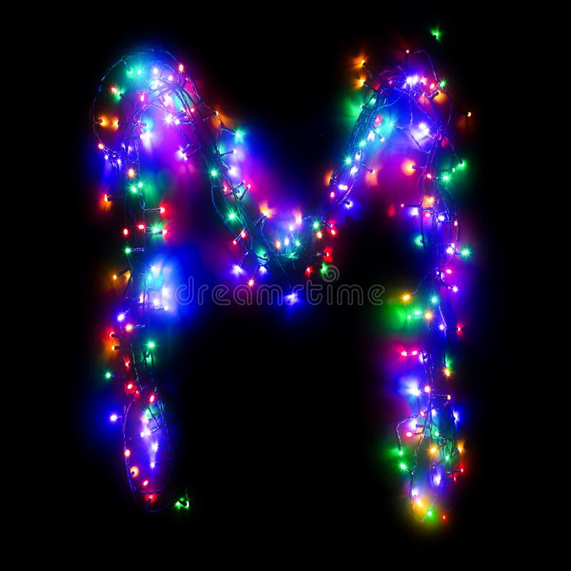 New Year`s alphabet. The letter `M` of the English alphabet from a multi-colored electric garland on a black isolated background. New Year`s alphabet. Wreath of stock photo