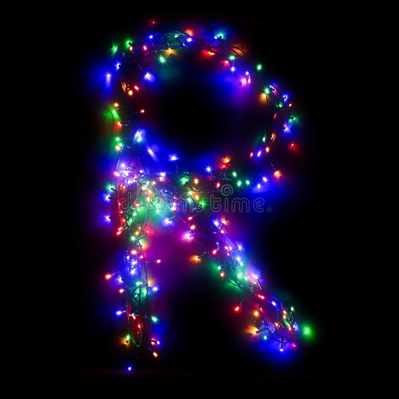 New Year`s alphabet. The letter `R` of the English alphabet from a multi-colored electric garland on a black isolated background. New Year`s alphabet.Wreath of stock photos