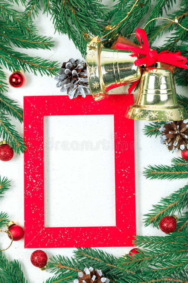 New Year`s background. Christmas jewelry on fir-tree branches, gold spheres, garlands and a red frame for a photo or an inscriptio royalty free stock images