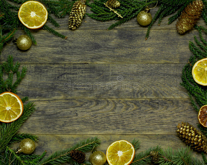 New Year`s border frame. Christmas wooden background. Border, frame from Christmas tree fir branches, gold pine cones, dried orange fruit slice on old wooden royalty free stock image