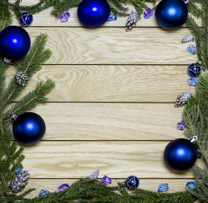 New Year`s border frame. Christmas wooden background. New Year`s border frame from Christmas tree fir branches, silver pine cones, blue balls on vertical old royalty free stock photos