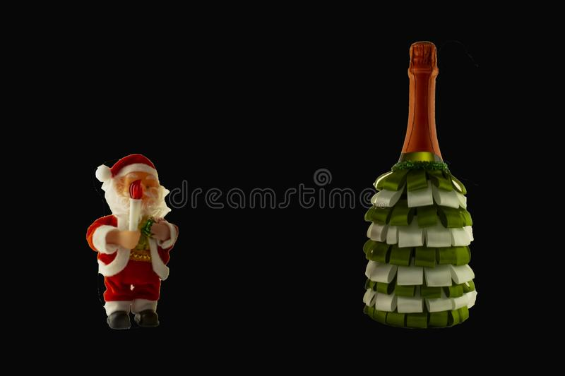 Christmas decoration champagne bottle with ribbons and Santa Claus on a black background. stock image