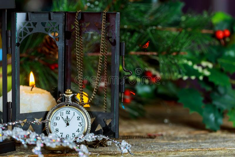 New Year s card with Christmas tree fir branches, midnight clock, burning candle, golden balls, garland lights on vertical old woo royalty free stock image