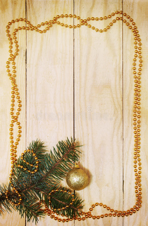 New Year's card,vertical. Christmas tree branch with golden ball and garland stock image