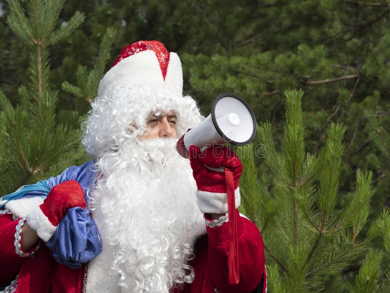 Father Frost shouts in the megaphone. The New Year`s character informs in a loud-hailer against the background of the nature stock photos