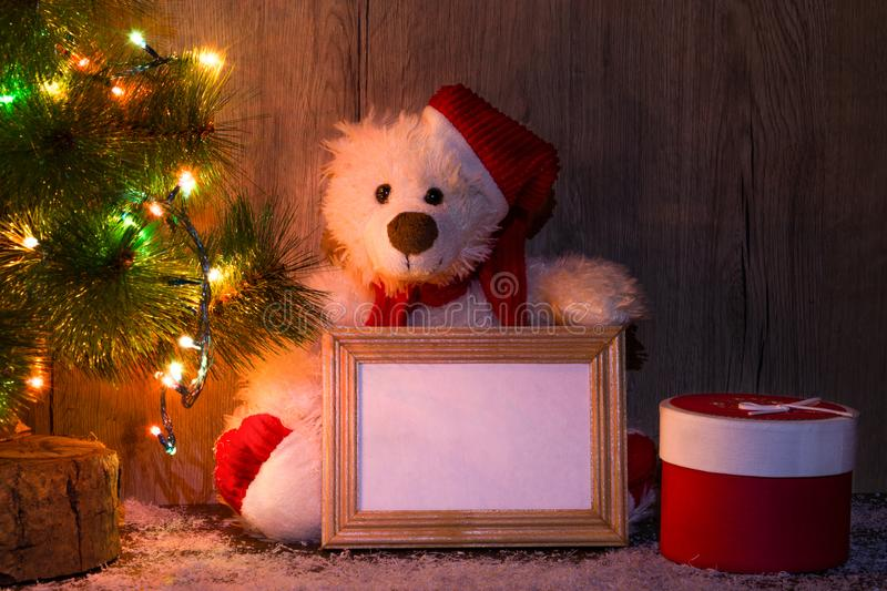 New Year`s, Christmas bear sitting under a fir tree with a wooden frame mockups for a photo or text. royalty free stock photography