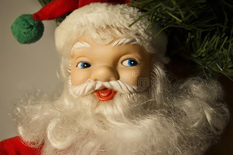 New Year`s Christmas soft toy figure smiling Santa Claus under the Christmas tree close up. Portrait royalty free stock photo