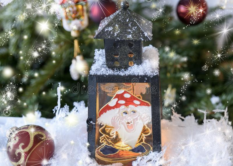 New Year`s, Christmas still life. Christmas handmade decorated lantern with a picture of fairy-tale amanita on the glass. Fir-tre. E background with lights stock photos