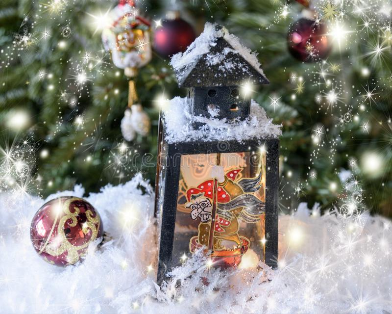 New Year`s, Christmas still life. Christmas handmade decorated lantern with a picture of fairy-tale Baba Yaga on the glass. Fir-t. Ree background with lights royalty free stock images