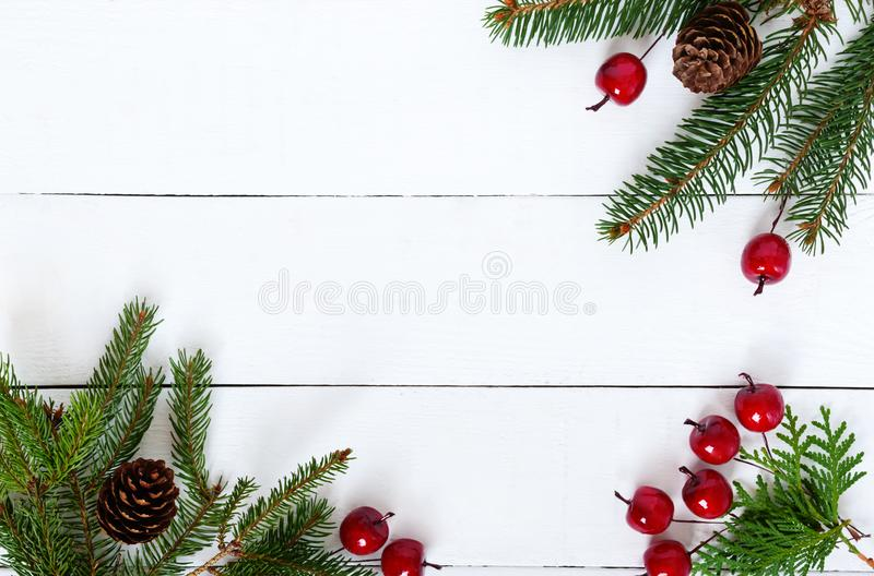 New Year`s, Christmas theme. Green fir branches with cones, decorative berries on white wooden background. Celebratory background. royalty free stock photography