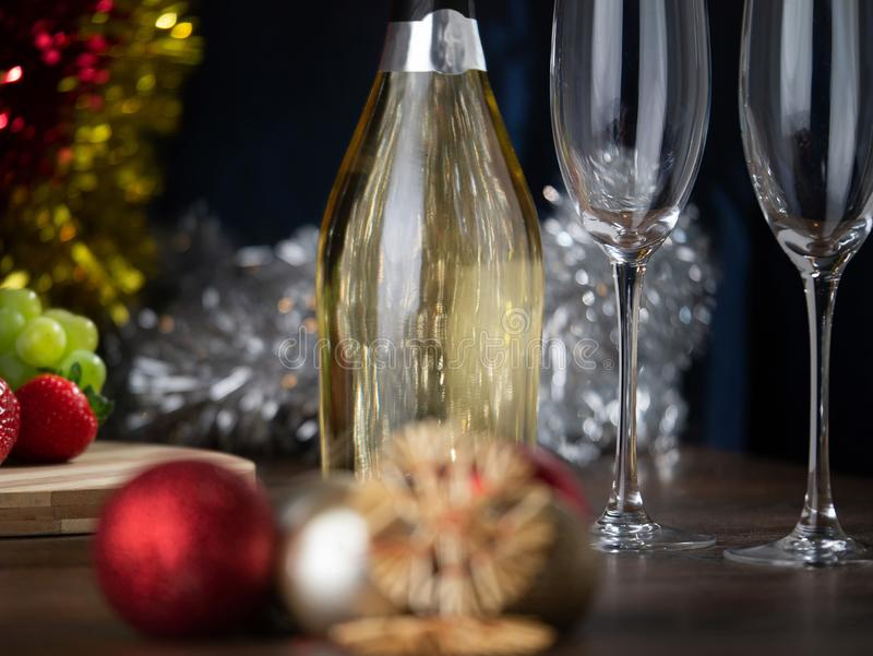 New Year``s and Christmas themed still life, Champagne bottle and flutes in focus, Decoration out of focus in boke stock image