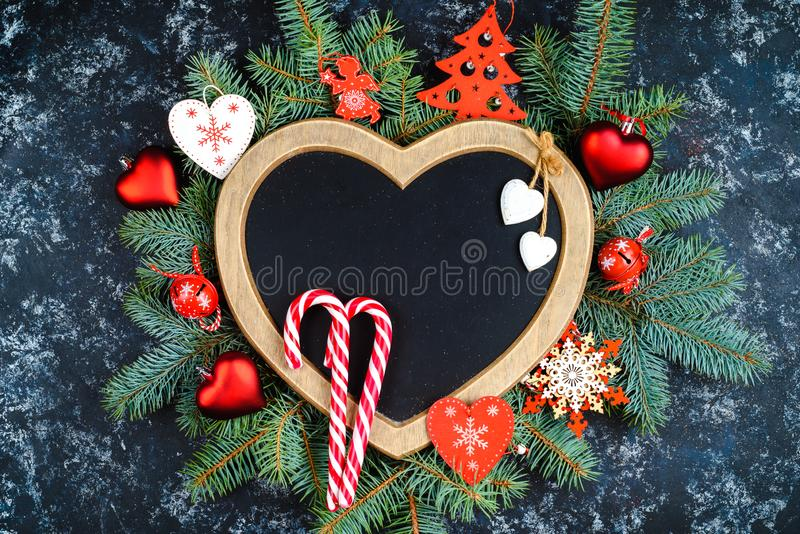New Year's composition of Christmas tree branches and Christmas tree decorations and a frame in the shape of a heart, top view, p. Lace for text stock photos