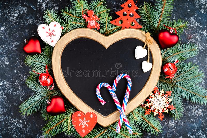 New Year's composition of Christmas tree branches and Christmas tree decorations and a frame in the shape of a heart, top view,. Old paper border with Christmas stock photos