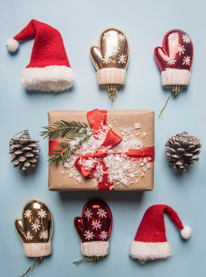 New Year`s concept, a box with a gift, Christmas-tree decorations are laid out on a blue background flat lay royalty free stock photos