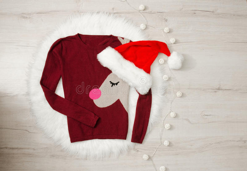 New Year`s concept sweater with reindeer and Santa`s hat. Garland, wood background. Space for text stock photography