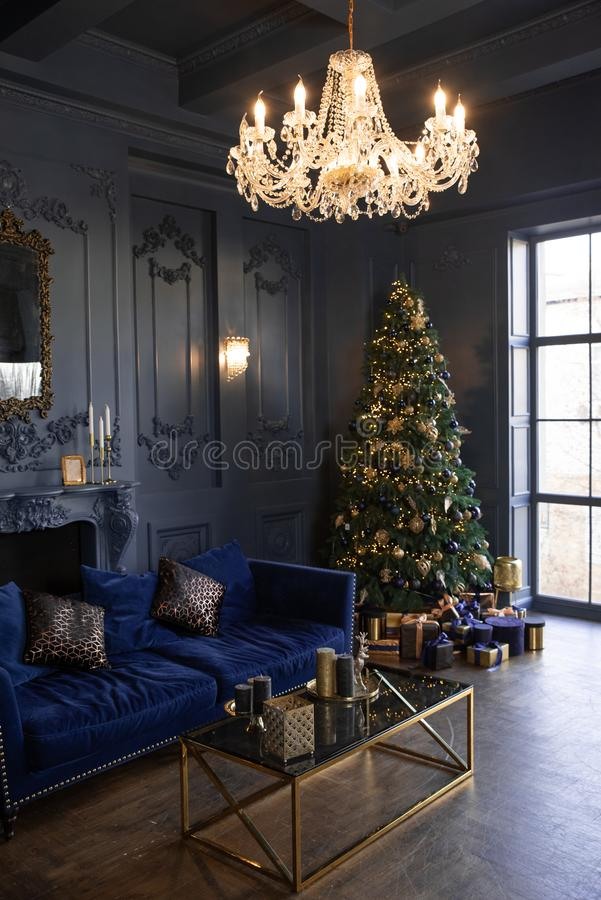 New Year`s decor and atmosphere in a large living room with dark walls. Christmas tree. Stylish modern living room stock photography