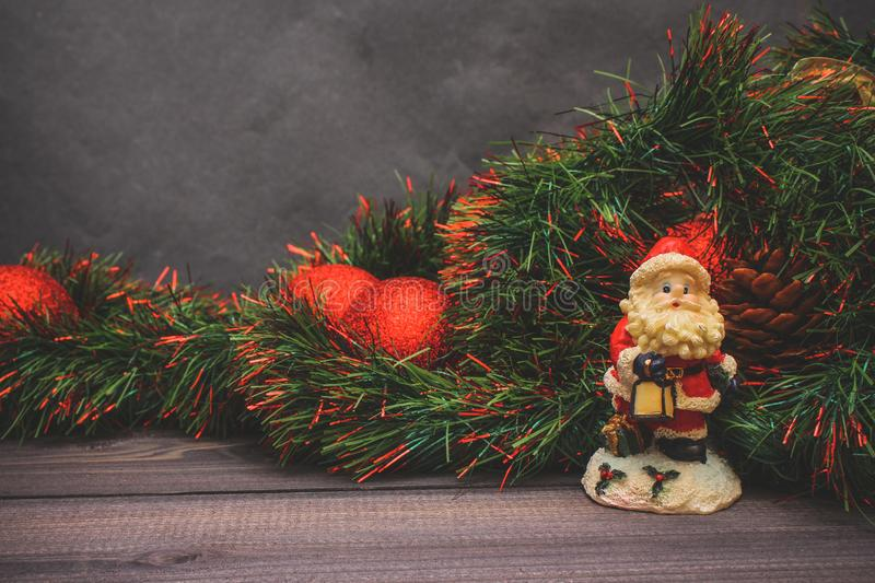 New Year`s decor and festive toys on a wooden table with a red string box with a gift Santa Claus.Happy New Year royalty free stock photography