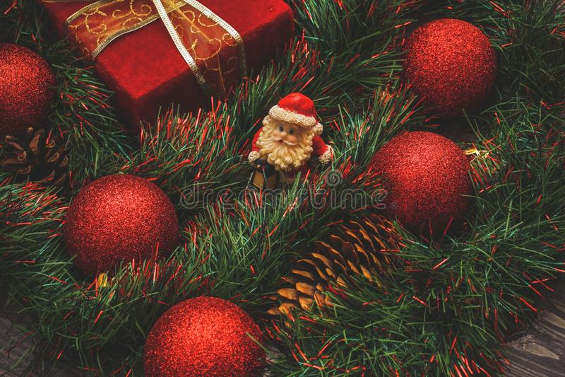 New Year`s decor and festive toys on a wooden table with a red string box with a gift Santa Claus.Happy New Year stock photography