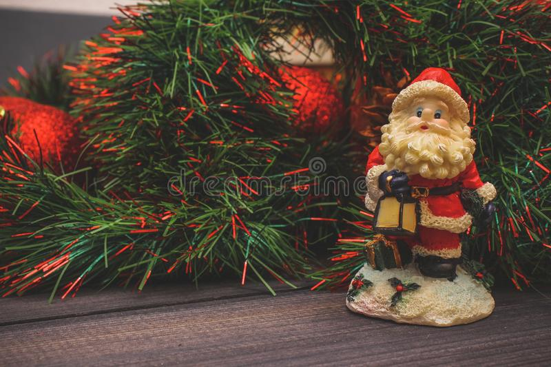 New Year`s decor and festive toys on a wooden table with a red string box with a gift Santa Claus.Happy New Year royalty free stock photos