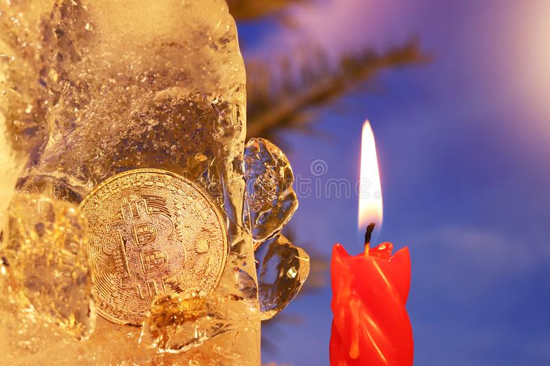 New Year`s decoration. Bitcoin sunk into the ice and brightened by the flame of a red candle against the background of Christmas. Tree branches and a blue sky stock photos