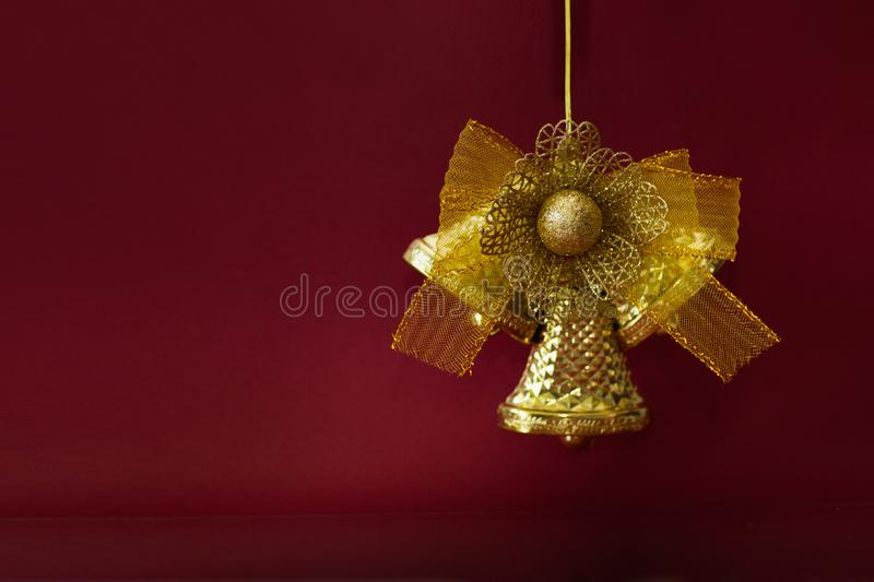 New Year`s decoration. Festive golden bell on a burgundy background with a space for text stock photo