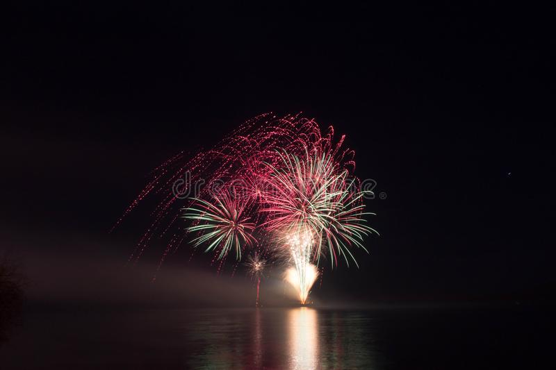 New Year`s Eve Fireworks launched from the water with reflections stock image