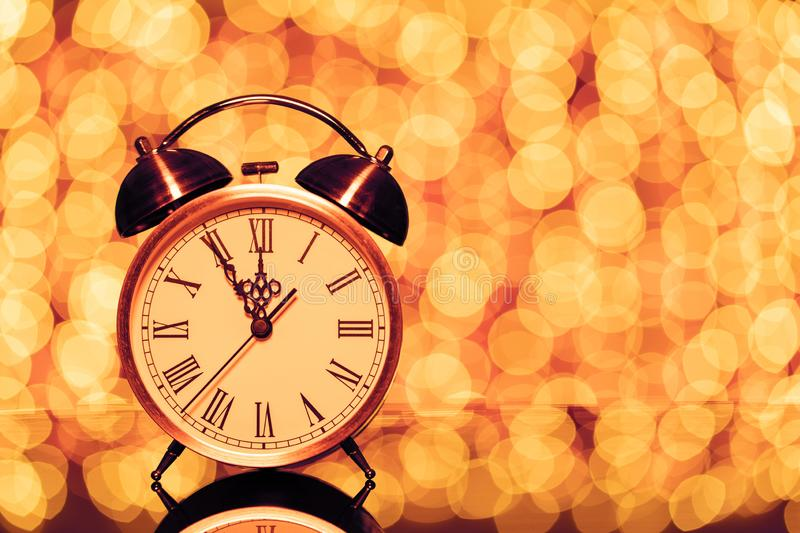 New year`s eve midnight. Retro alarm clock whose pointer shows five to twelve on festive bokeh background. New year`s eve midnight. Vintage alarm clock whose stock photography