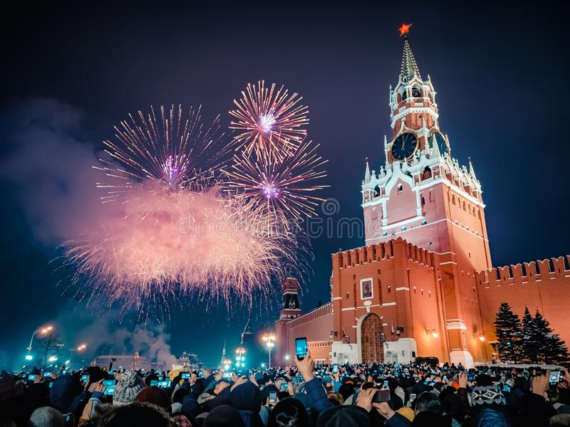 New Year`s Eve in Moscow. Fireworks on Red Square near the Spasskaya Tower on New Year`s Eve. Multicolored salute in the. Kremlin. A large crowd of people stock image