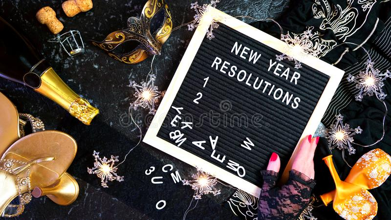 New Year`s Eve resolutions letter board and black and gold party decorations. New Year`s Eve resolutions flatlay with letter board and black and gold party stock image