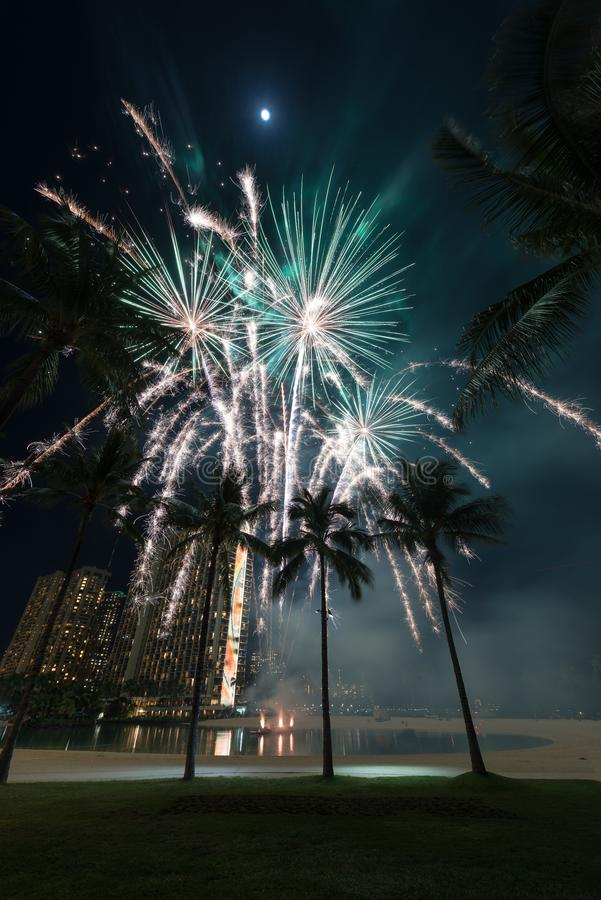 New Year`s fireworks in Honolulu, Hawaii. New Year's fireworks at the Hilton Hawaiian Village in Honolulu, Hawaii with the beach, palm trees and a lagoon royalty free stock images