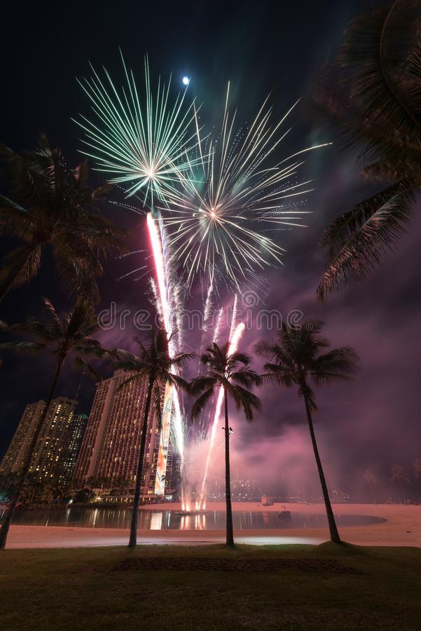 New Year`s fireworks in Honolulu, Hawaii. New Year's fireworks at the Hilton Hawaiian Village in Honolulu, Hawaii with the beach, palm trees and a lagoon stock image
