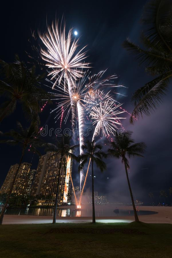 New Year`s fireworks in Honolulu, Hawaii. New Year's fireworks at the Hilton Hawaiian Village in Honolulu, Hawaii with the beach, palm trees and a lagoon royalty free stock photography