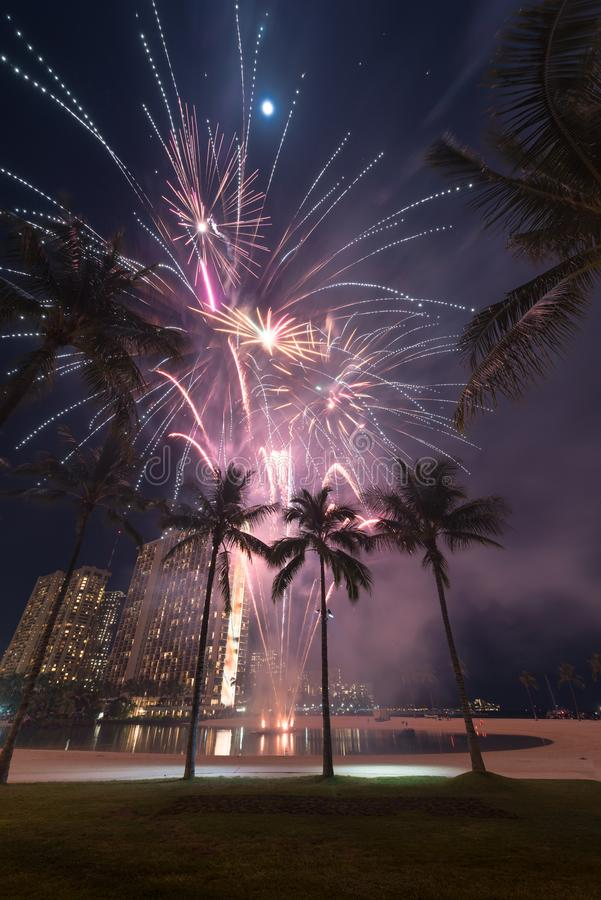 New Year`s fireworks in Honolulu, Hawaii. New Year's fireworks at the Hilton Hawaiian Village in Honolulu, Hawaii with the beach, palm trees and a lagoon stock images