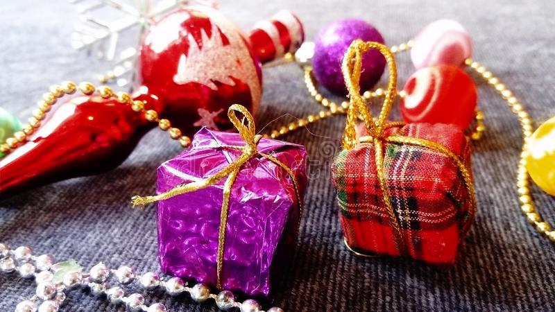 New Year`s gifts and decorations. Bright, multi-colored, shiny boxes and balls on a gray background.  royalty free stock images