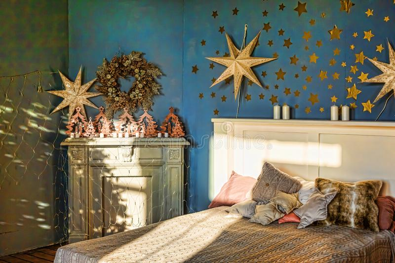 New Year`s interior. Bedroom with fireplace decorated with Christmas stars. Sweet home, family holiday concept royalty free stock photography