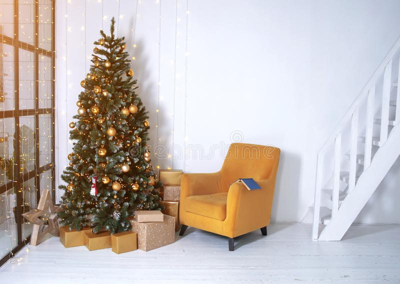 New year`s interior. Decorated Christmas tree in the interior of the living room. The blue book is on the yellow chair. White walls in the interior stock photo