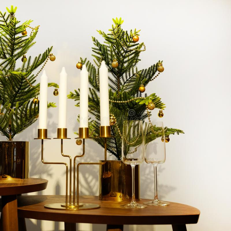 New year`s interior. A small artificial Christmas tree with toys and candles. Glasses serving royalty free stock photos