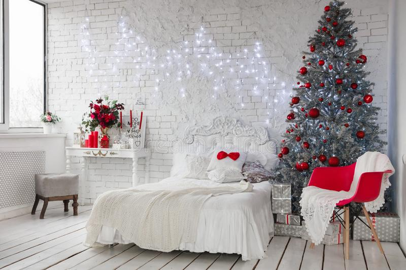 New Year`s interior, a white photo studio with a silver Christmas tree and a white bed, red Christmas tree decorations royalty free stock image