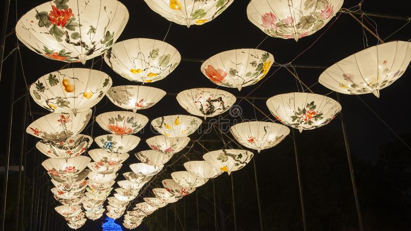 Creative lighting. In the New Year`s Lantern Festival, the lighting made of umbrellas with Chinese paintings is colorful and creative
