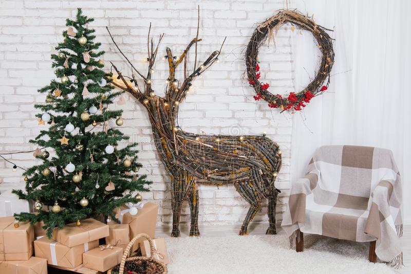 New Year`s location in the studio with a deer, decorated with a Christmas tree, gifts, a basket of cones stock photo