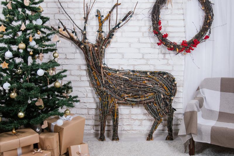 New Year`s location in the studio with a deer, decorated with a Christmas tree, gifts, a basket of cones royalty free stock image