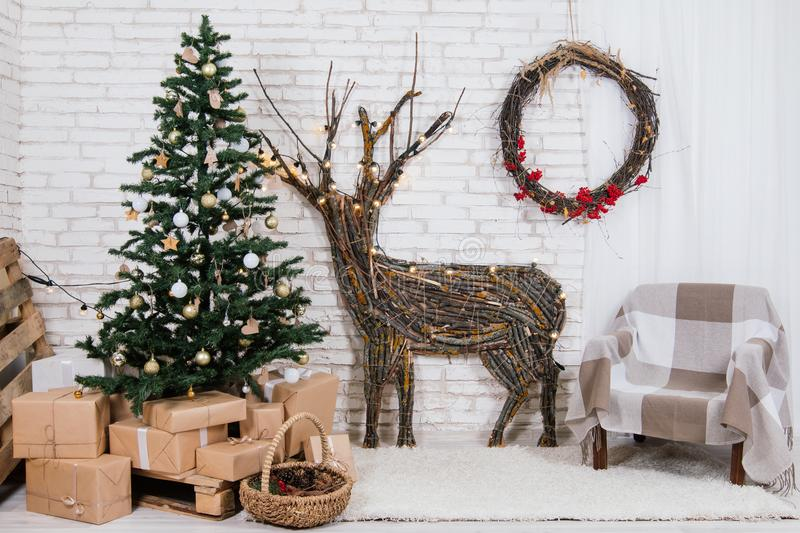 New Year`s location in the studio with a deer, decorated with a Christmas tree, gifts, a basket of cones stock images