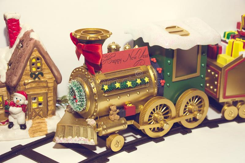 New Year`s locomotive runs along the rails past a beautiful New Year`s house, next to which there is a snowman. royalty free stock photography