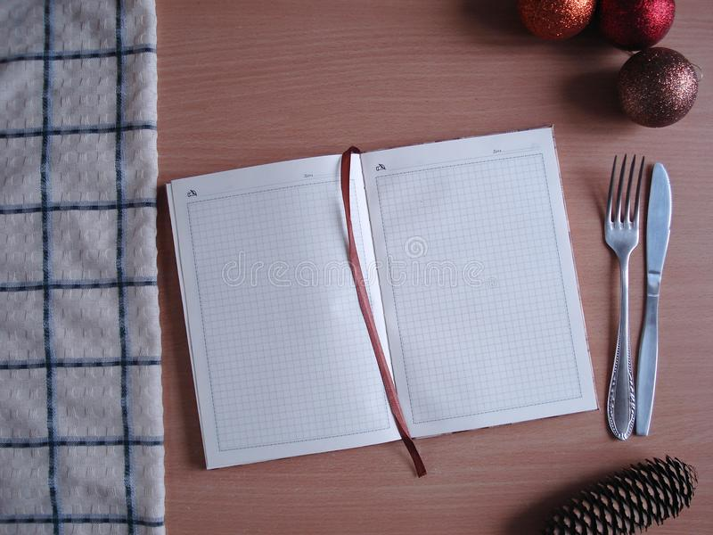 New Year`s menu. Notepad, towel, Christmas toys on the table. stock image
