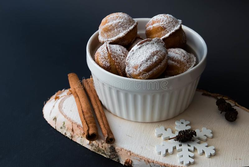 New Year`s nuts with condensed milk and cinnamon, with a snowflake, on a black background stock images