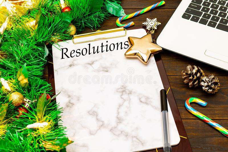 2019 New Year`s Resolutions and laptop with christmas tree branches, golden star, candy cane, cones on wooden background stock photo